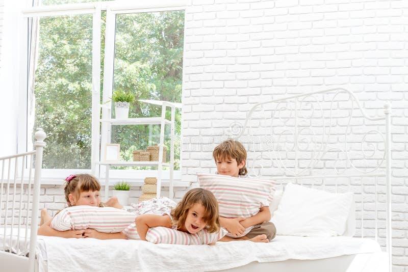 Τρία μικρά ευτυχή παιδιά που παίζουν στο κρεβάτι στο σπίτι στοκ εικόνες