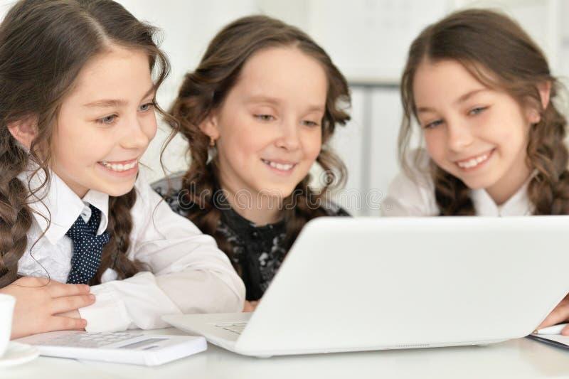Τρία μικρά κορίτσια που χρησιμοποιούν ένα lap-top στοκ φωτογραφίες