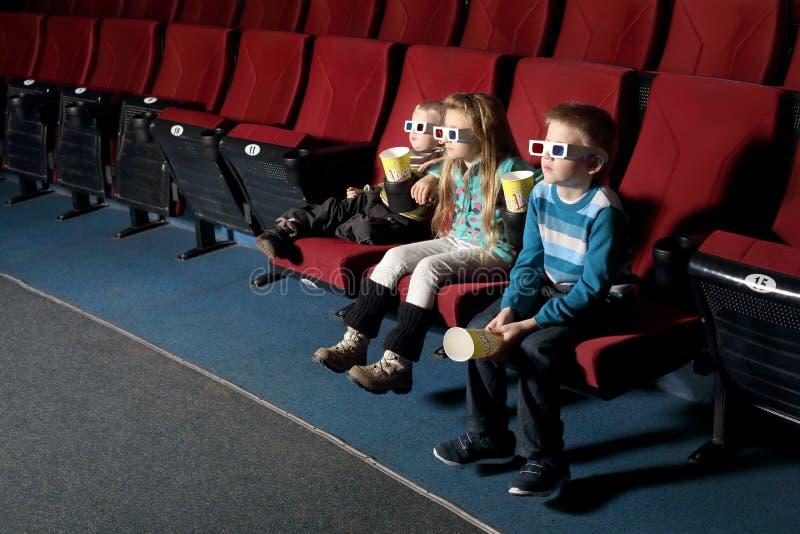 Τρία μικρά παιδιά στα τρισδιάστατα γυαλιά που προσέχουν έναν κινηματογράφο στοκ φωτογραφίες