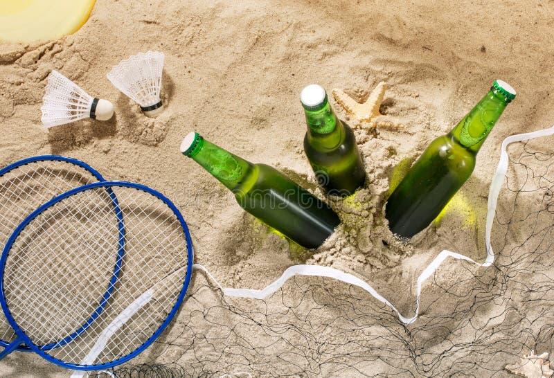 Τρία μπουκάλια της κρύας ελαφριάς μπύρας στην άμμο, τοπ άποψη στοκ εικόνες με δικαίωμα ελεύθερης χρήσης