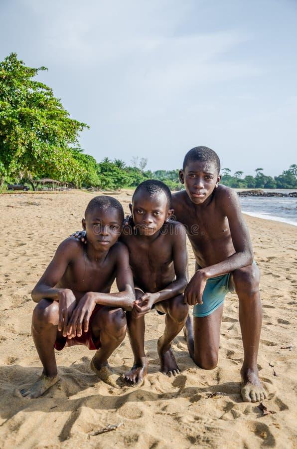 Τρία νέα αφρικανικά αγόρια που θέτουν για μια φωτογραφία στην παραλία κοντά σε Kribi ποτίζουν τις πτώσεις, Καμερούν, κεντρική Αφρ στοκ εικόνες με δικαίωμα ελεύθερης χρήσης