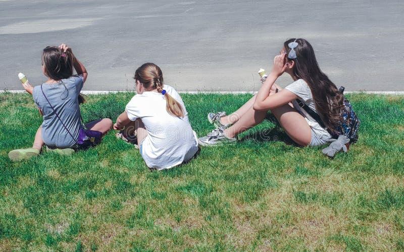 Τρία νέα κορίτσια που κάθονται στη χλόη, οπισθοσκόπο στοκ φωτογραφία