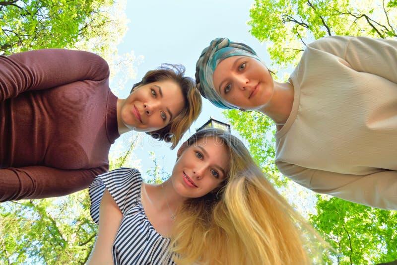 Τρία νέα κορίτσια που κλίνουν στο πλαίσιο ενάντια στον ουρανό στο PA στοκ εικόνες