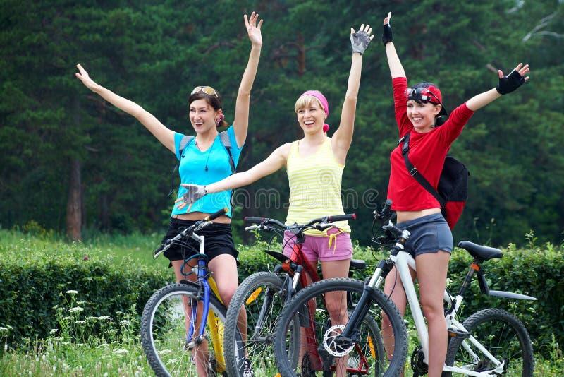 Τρία νέα κορίτσια στο ποδήλατο στοκ εικόνες με δικαίωμα ελεύθερης χρήσης