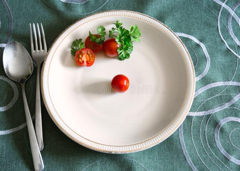 Τρία ντομάτες κερασιών και φύλλα μαϊντανού στο άσπρο πιάτο στοκ εικόνες