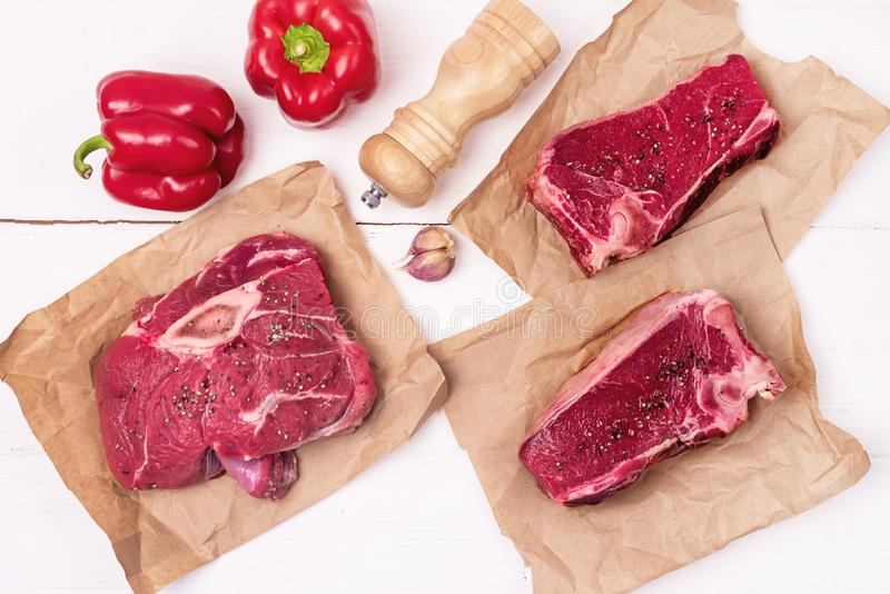 Τρία Νωπά Κρέατα Από Νωπό Βοδινό Κρέας Από Βιοτεχνικό Χαρτί Μπριζόλα Λευκό Ξύλινο Φόντο Ώριμο Κόκκινο Πιπέρι Ξύλινο Πιπέρι Μύλος στοκ εικόνα με δικαίωμα ελεύθερης χρήσης
