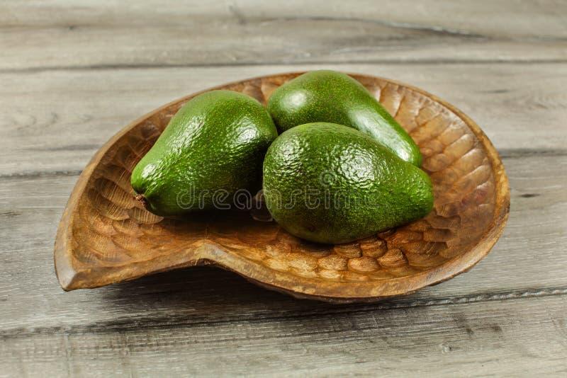 Τρία ολόκληρα αχλάδια αβοκάντο στο ξύλινο κύπελλο, στον αγροτικό πίνακα στοκ φωτογραφίες με δικαίωμα ελεύθερης χρήσης