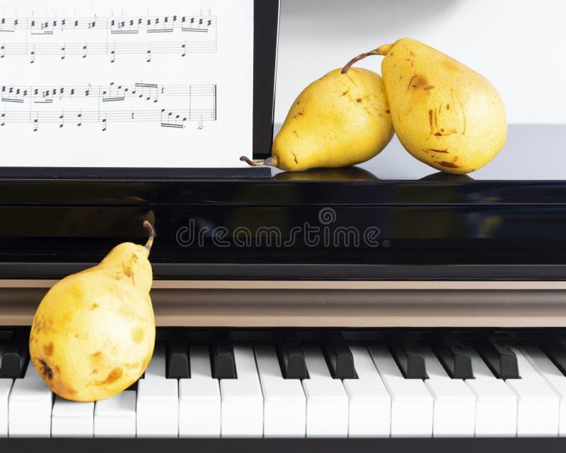 Τρία οργανικά κίτρινα αχλάδια που τοποθετούνται στο κλειδί πιάνων στοκ φωτογραφία με δικαίωμα ελεύθερης χρήσης