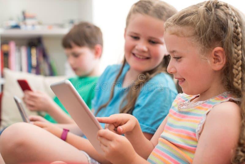 Τρία παιδιά στον καναπέ που παίζει στο σπίτι με τις ψηφιακές συσκευές στοκ φωτογραφία με δικαίωμα ελεύθερης χρήσης