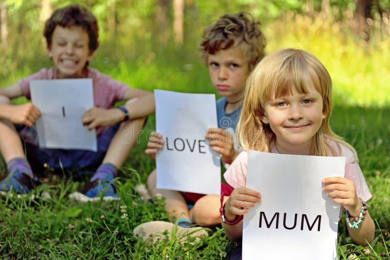 Τρία παιδιά με το σημάδι Ι αγάπη mum στοκ φωτογραφίες