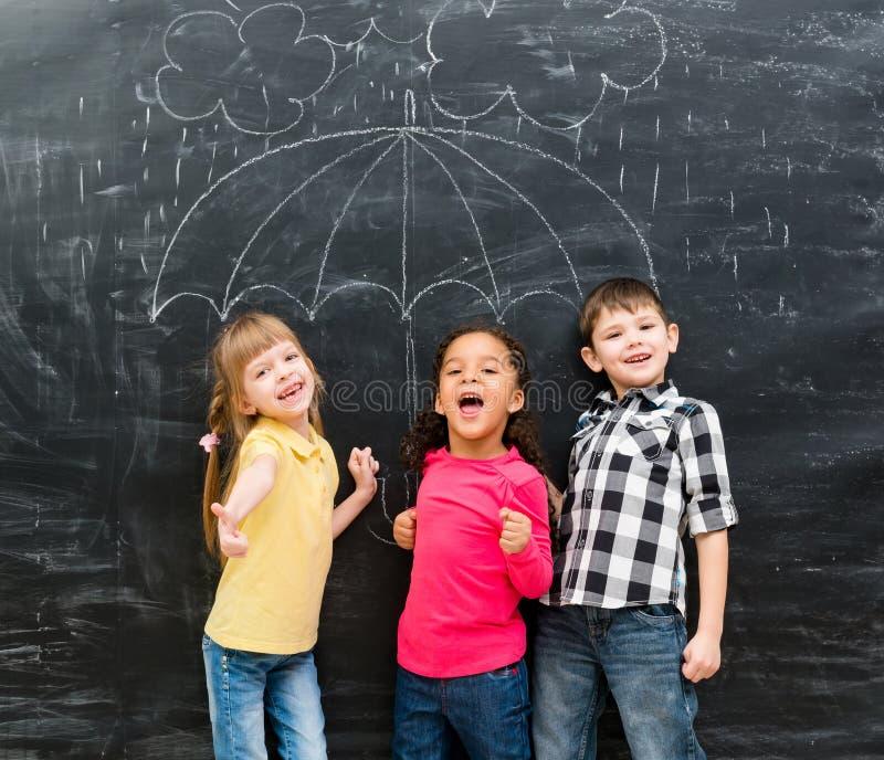 Τρία παιδιά που στέκονται κάτω από τη συρμένη ομπρέλα στοκ φωτογραφία με δικαίωμα ελεύθερης χρήσης