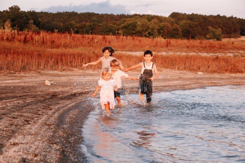 Τρία παιδιά που τρέχουν κατά μήκος της παραλίας στοκ εικόνα