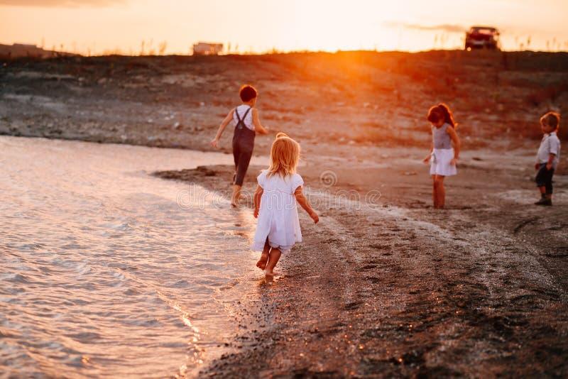 Τρία παιδιά που τρέχουν κατά μήκος της παραλίας στοκ εικόνα με δικαίωμα ελεύθερης χρήσης