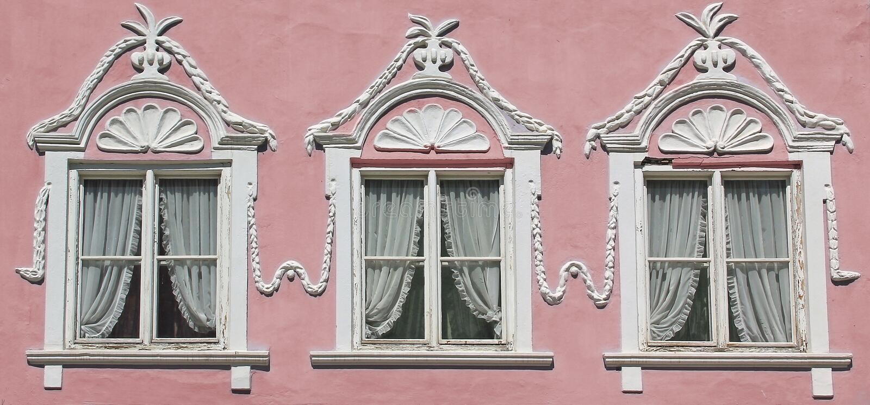Τρία παράθυρα στο ρόδινο τοίχο σπιτιών με το στόκο περίκομψο στοκ φωτογραφία με δικαίωμα ελεύθερης χρήσης