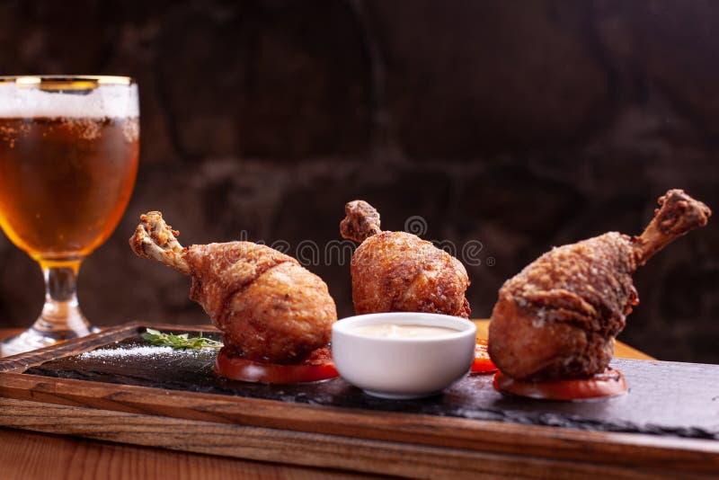 Τρία πασπαλισμένα με ψίχουλα πόδια κοτόπουλου στις σαλτσιέρες, στάση στη μαύρη πλάκα Μαύρο υπόβαθρο, όμορφο φως στοκ φωτογραφίες με δικαίωμα ελεύθερης χρήσης