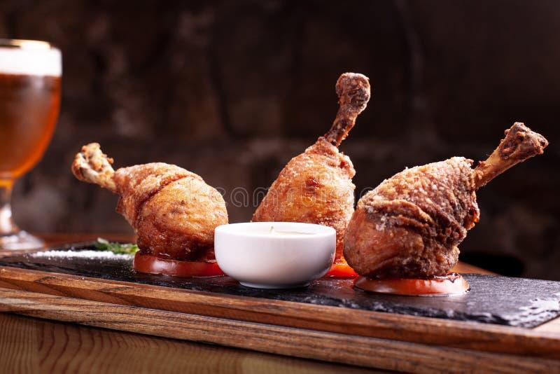 Τρία πασπαλισμένα με ψίχουλα πόδια κοτόπουλου στις σαλτσιέρες, στάση στη μαύρη πλάκα Μαύρο υπόβαθρο, όμορφο φως στοκ εικόνα