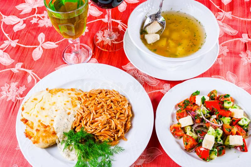 Τρία πιάτα με τα πιάτα μεσημεριανού γεύματος στον πίνακα Η φυτική σαλάτα, η σούπα ψαριών και το κοτόπουλο schnitzel με συλλαβισμέ στοκ εικόνα με δικαίωμα ελεύθερης χρήσης
