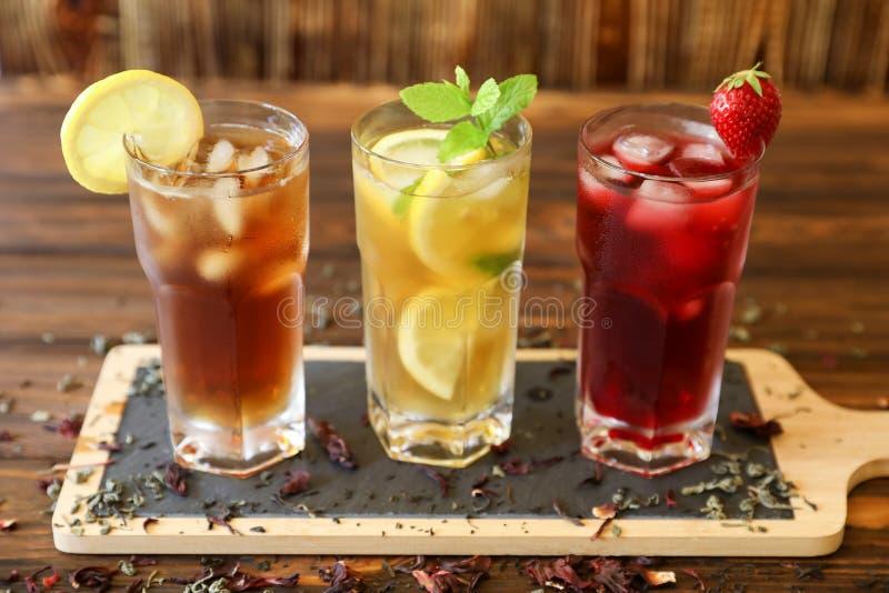 Τρία ποτήρια του διαφορετικού κρύου τσαγιού πίνουν το Μαύρο, πράσινο με το λεμόνι και τη μέντα, hibiscus τσάγια στοκ εικόνα