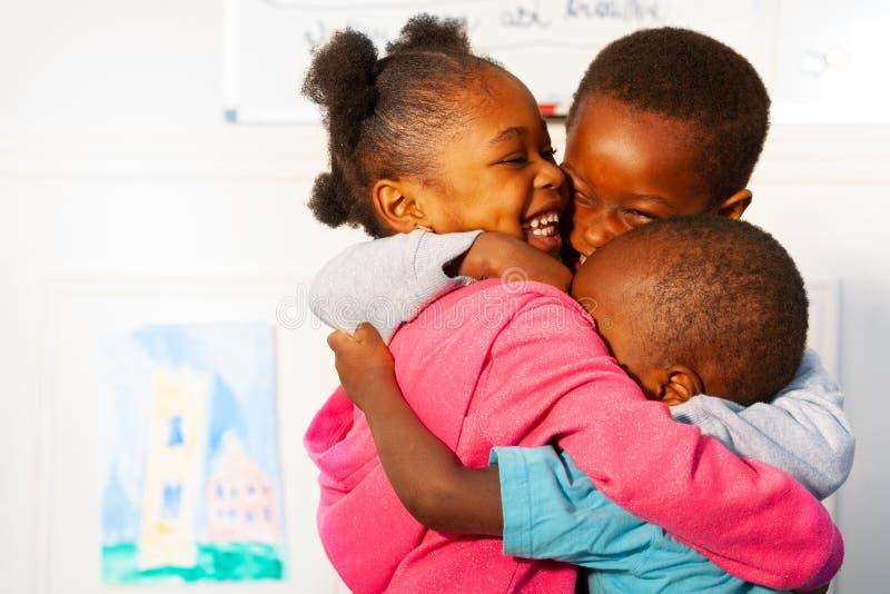 Τρία που αγκαλιάζουν τα στενά μαύρα παιδιά στην κατηγορία βρεφικών σταθμών στοκ εικόνες