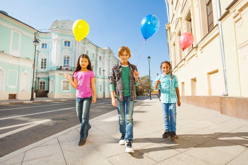 Τρία πολυεθνικά παιδιά με τα ζωηρόχρωμα μπαλόνια στοκ εικόνες