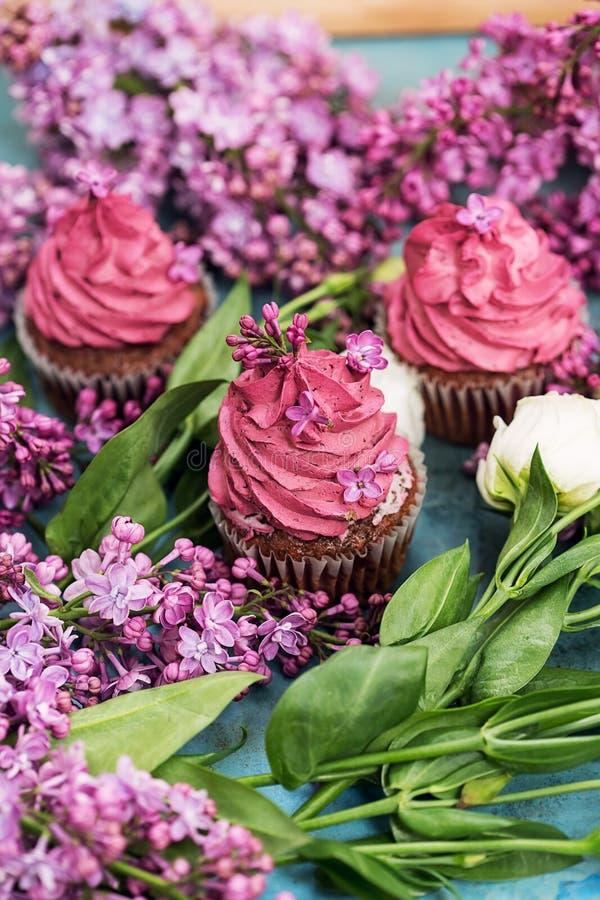 Τρία ρόδινα cupcakes με την πορφυρή πασχαλιά και άσπρος αυξήθηκαν στοκ φωτογραφία με δικαίωμα ελεύθερης χρήσης