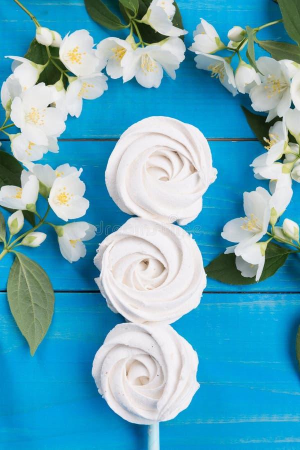 Τρία σπιτικά marshmallows μήλων που βρίσκονται σε μια σειρά στις μπλε επιτροπές, που διακοσμούνται με τα λουλούδια, μια έννοια εν στοκ φωτογραφία με δικαίωμα ελεύθερης χρήσης