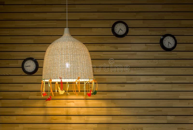 Τρία στρογγυλά μαύρα ρολόγια στον τοίχο των ξύλινων ανοικτό γκρι κίτρινων πινάκων με μεγάλο ψάθινο lampshade οριζόντιες γραμμές r στοκ φωτογραφίες