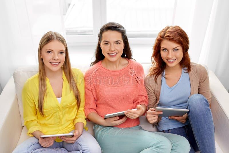 Τρία χαμογελώντας έφηβη με το PC ταμπλετών στο σπίτι στοκ εικόνες