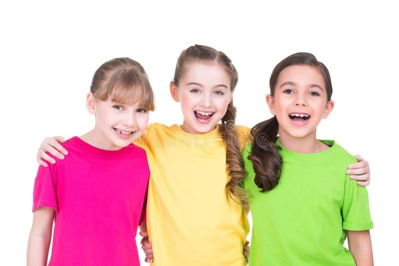 Τρία χαριτωμένα μικρά χαριτωμένα χαμογελώντας κορίτσια στις ζωηρόχρωμες μπλούζες στοκ φωτογραφία