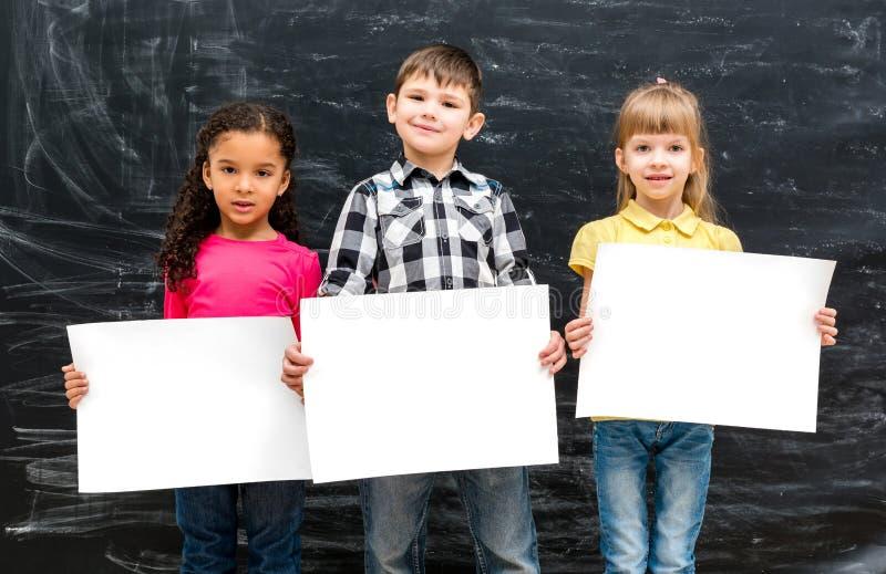 Τρία χαριτωμένα παιδιά με τα κενά φύλλα εγγράφου στα χέρια στοκ φωτογραφία με δικαίωμα ελεύθερης χρήσης