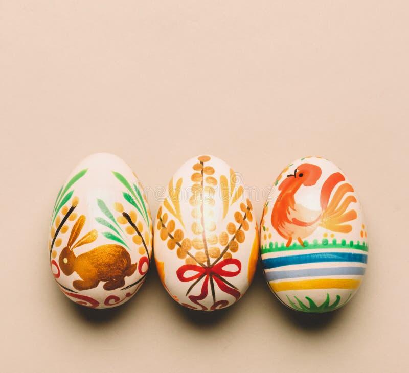 Τρία χειροποίητα αυγά Πάσχας στο κρεμώδες υπόβαθρο στοκ εικόνες