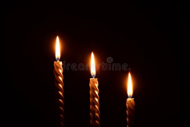 Τρία χρυσά κεριά σε ένα μαύρο υπόβαθρο στοκ φωτογραφία