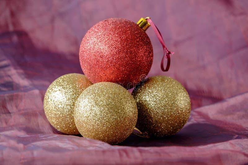 Τρία χρυσά μπιχλιμπίδια Χριστουγέννων με ένα κόκκινο στοκ φωτογραφίες