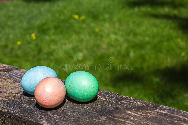 Τρία χρωματισμένα αυγά Πάσχας που κάθονται σε ένα κιγκλίδωμα στοκ εικόνες
