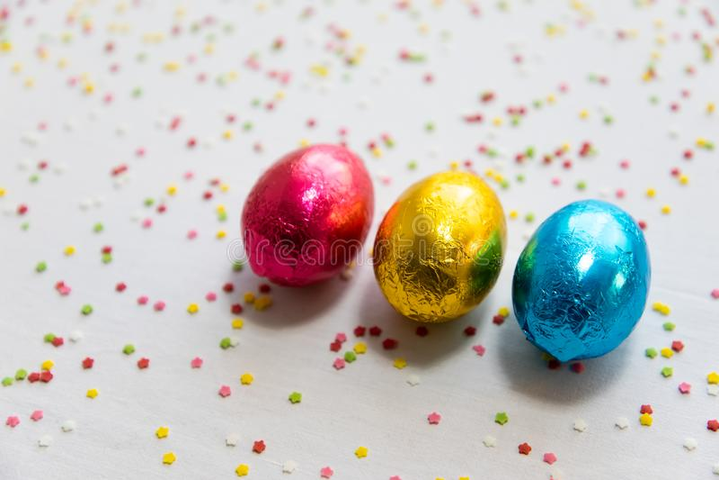 Τρία χρωματισμένα αυγά Πάσχας σοκολάτας στο άσπρο υπόβαθρο και το ζωηρόχρωμο κομφετί στοκ φωτογραφία