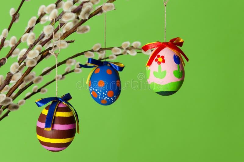 Τρία χρωματισμένα αυγά Πάσχας στην ανθοδέσμη ιτιών με τις ιτιές γατών στοκ εικόνες