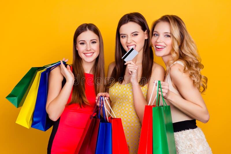 Τρία όμορφα, γοητευτικά, επιτυχή κορίτσια που κρατούν το ζωηρόχρωμο shopp στοκ φωτογραφίες