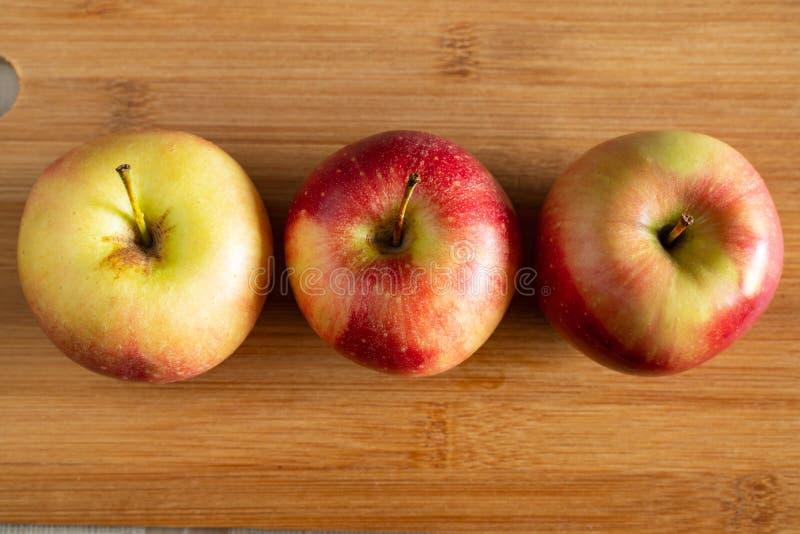 τρία όμορφα κόκκινος-κίτρινα μήλα που βρίσκονται σε ένα ξύλινο υπόβαθρο στοκ φωτογραφία