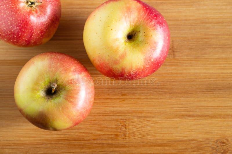 τρία όμορφα κόκκινος-κίτρινα μήλα που βρίσκονται σε ένα ξύλινο υπόβαθρο τριγώνων στοκ εικόνες με δικαίωμα ελεύθερης χρήσης