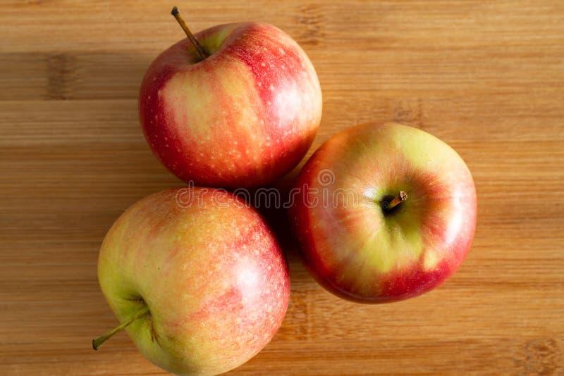 τρία όμορφα κόκκινος-κίτρινα μήλα που βρίσκονται σε ένα ξύλινο υπόβαθρο τριγώνων στοκ φωτογραφίες