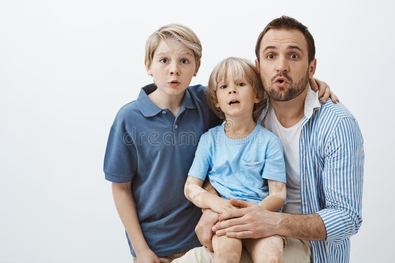 Τρία όμορφα οικογενειακά μέλη που στέκονται πέρα από τον γκρίζο τοίχο, κάνοντας τις έκπληκτες και κατάπληκτες εκφράσεις αγκαλιάζο στοκ φωτογραφία με δικαίωμα ελεύθερης χρήσης