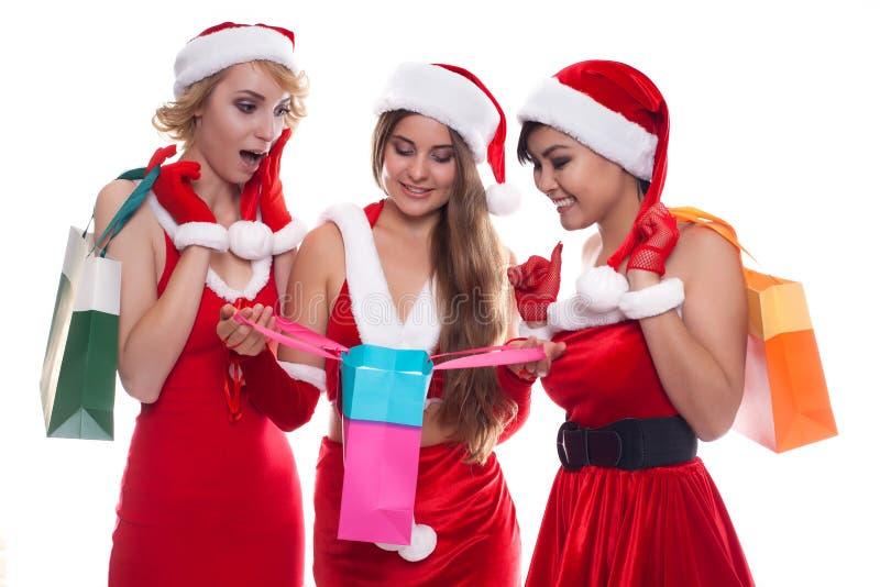 Τρία όμορφα προκλητικά κορίτσια που φορούν τα ενδύματα Άγιου Βασίλη με το κατάστημα στοκ φωτογραφία με δικαίωμα ελεύθερης χρήσης
