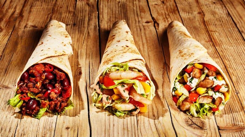 Τρία burritos κρέατος στον πίνακα στοκ εικόνα