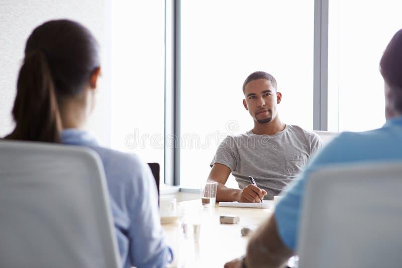 Τρία Businesspeople που διοργανώνουν τη συνεδρίαση στην αίθουσα συνεδριάσεων στοκ φωτογραφία με δικαίωμα ελεύθερης χρήσης