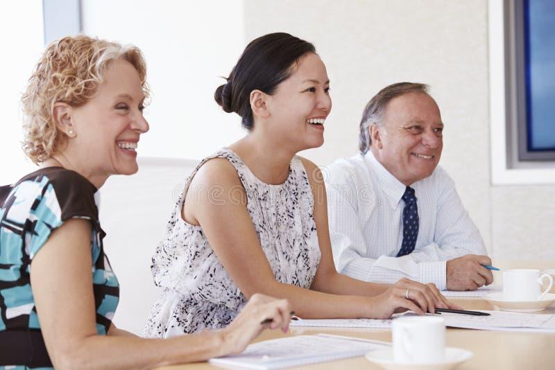 Τρία Businesspeople που διοργανώνουν τη συνεδρίαση στην αίθουσα συνεδριάσεων στοκ φωτογραφία