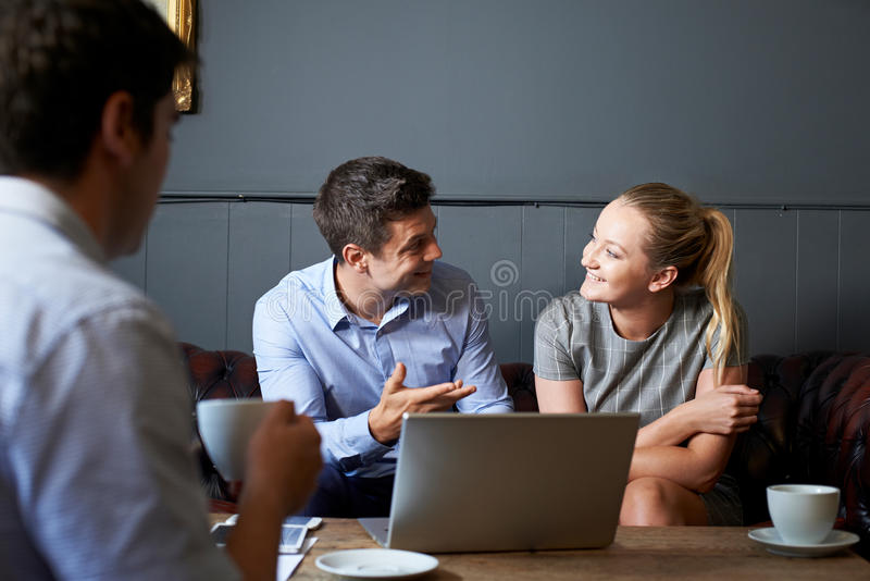 Τρία Businesspeople που διοργανώνουν τη συνεδρίαση στον καφέ στοκ φωτογραφίες