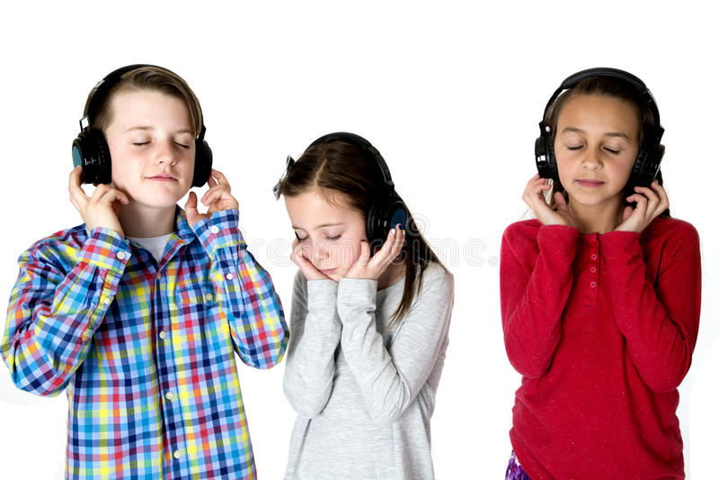 Τρία preteens που ακούνε τη μουσική με τις προσοχές ακουστικών ιδιαίτερες στοκ εικόνες