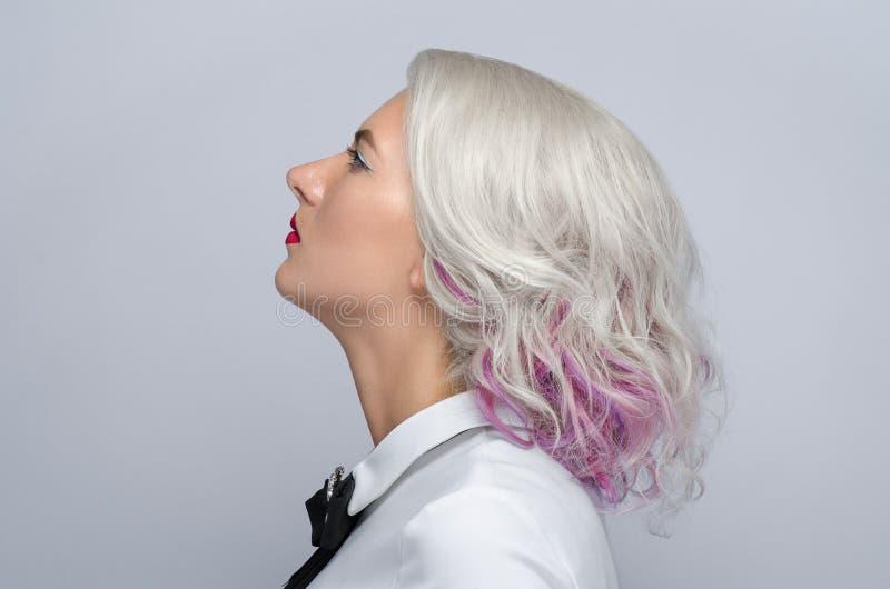 Τρίχα και θέμα σύνθεσης: όμορφη νέα ξανθή γυναίκα με το δημιουργικό προσδιορισμό τρίχας με τα κόκκινα χείλια στο γκρίζο υπόβαθρο  στοκ φωτογραφίες με δικαίωμα ελεύθερης χρήσης