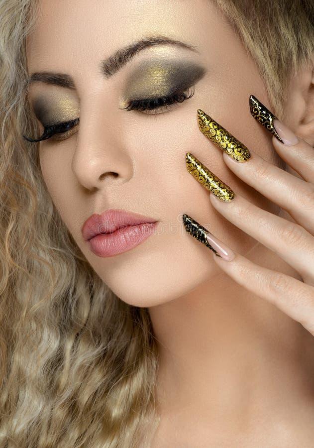 Τρίχα και θέμα σύνθεσης: όμορφο κορίτσι με το όμορφο χρυσό καρφί στο στούντιο στοκ εικόνες με δικαίωμα ελεύθερης χρήσης