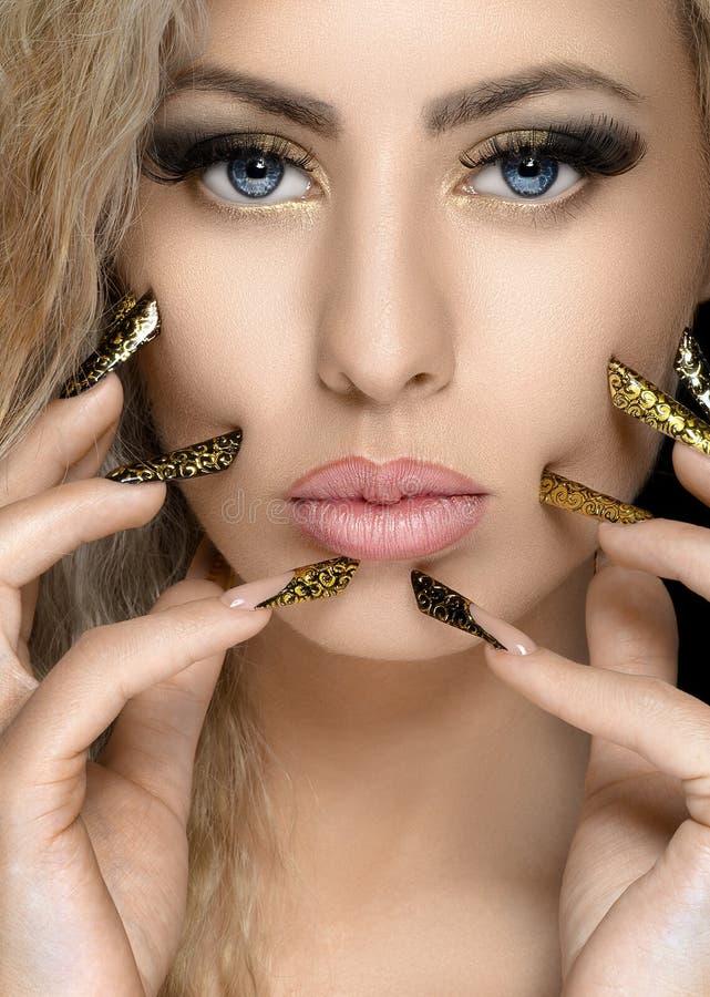 Τρίχα και θέμα σύνθεσης: όμορφο κορίτσι με το όμορφο χρυσό καρφί στο στούντιο στοκ εικόνα